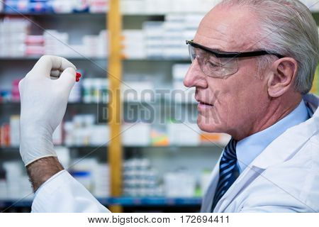 Pharmacist checking a capsule in pharmacy