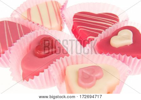 Close-up of a pink heart shaped petit fours cakes seen from the side on a white background
