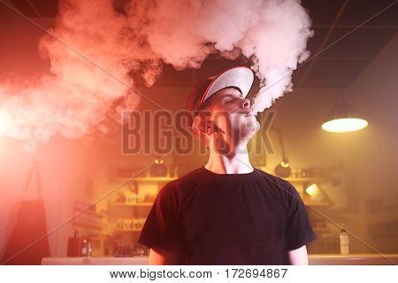 Vape. Vaping man in a cloud of vapor. Photo is taken in a vape bar.