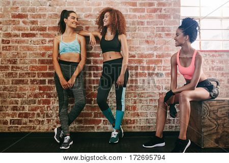 Three Young Women Resting After Exercise In Gym