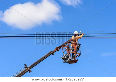 Electrician at height in bucket of hydraulic lift platform truck installing new high voltage power lines.