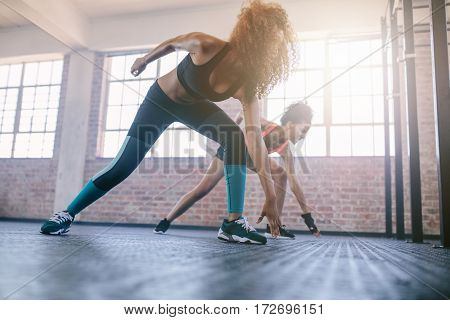 Shot of young females running in the gym. Women doing fitness workout in healthclub.