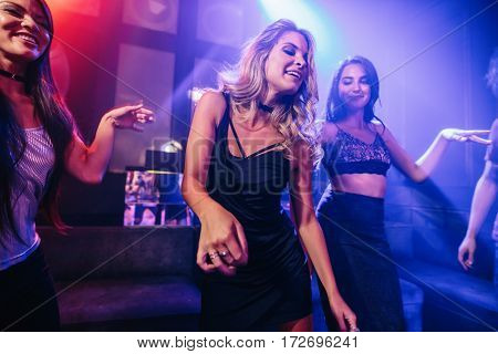 Young clubber dancing surrounded by her friends. Group of young women dancing at disco.