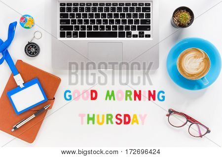 Caption word Good morning thursday. White office desk with laptop diary eyeglasses compass pen blank identification card and cup of coffee on white background.