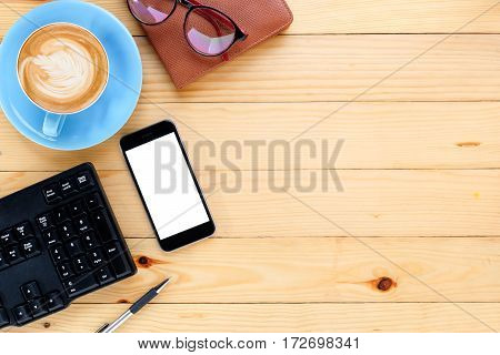 Office desk table with blank screen smartphonecup of coffeekeyboardpeneyeglasses and leather notebook.Top view with copy space.