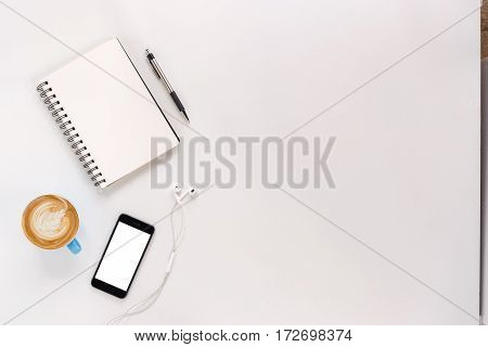 Modern White office desk table with blank screen smart phonenotebookpen and cup of coffee.Top view with copy space.Working desk table concept.