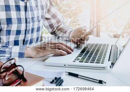 Businessman working laptop computer and using smart phone in hands touching on a screen.Business concept
