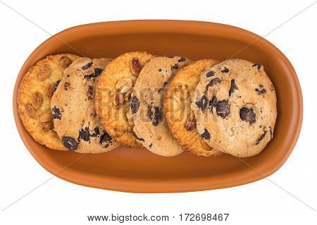 Cookies with peanuts and chocolate in a brown plate. Isolated on white background. Top view.