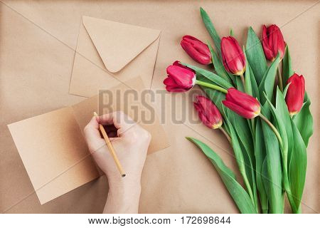 Spring tulip flowers and man hand signing a card on brown background top view in flat lay style. Greeting for Birthday Womans or Mothers Day.