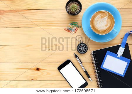 Office desk table with notebooksmart phonepenname card and cup of coffee.Top view with copy space.Office desk table concept.