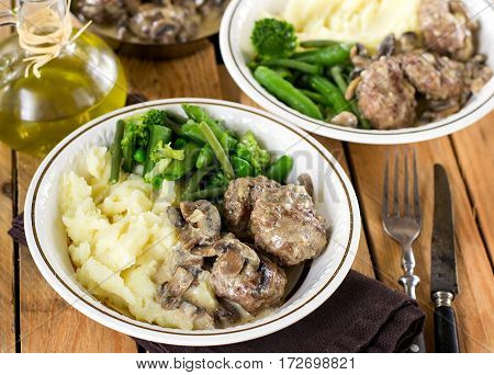 Beef and veal meatballs in creamy mushroom sauce served with vegetables