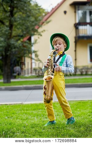 Little boy in dancing suit plays saxophone on grassy lawn against two-storied house.
