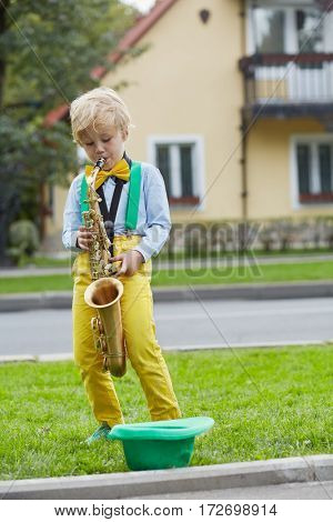 Little boy in dancing suit plays saxophone on grassy lawn against two-storied house near road, hat for earnings lies on grass.