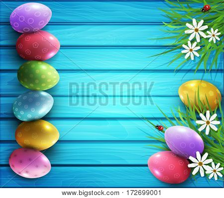 background for Easter. Colored eggs, flowers, daisies, grass lying on a blue wooden board