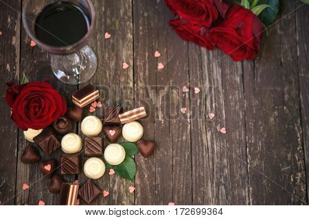 Old wooden background with red roses and chocolate pralines copy space top view
