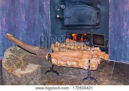 Interior fireplace in a corner with firewood and ax in an old country house