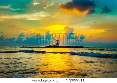 sunset and beach. Beautiful sunset above the sea and lighthouse on the rock
