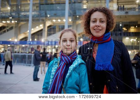 Woman and girl in red-and-blue scarfs stand at entrance to stadium.