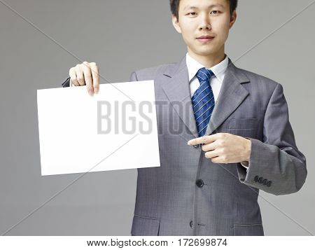 asian business executive in suit holding a piece of blank white paper gray background.
