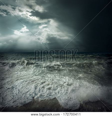 View of great storm on the sea. Strong wind and big waves with splash drops under dark sky.
