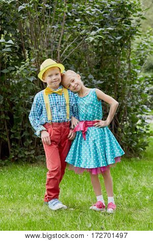 Boy and girl dressed in bright dancing suits pose at grassy lawn.