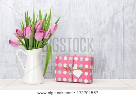 Fresh pink tulip flowers bouquet and gift box on shelf in front of wooden wall