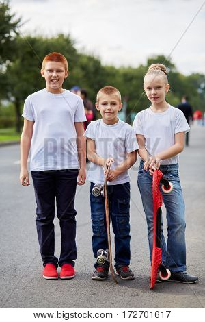 Two boys and girl stand with skateboards on road.