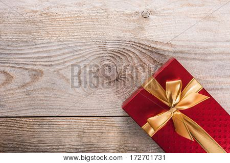Gift box with satin ribbon on wooden background