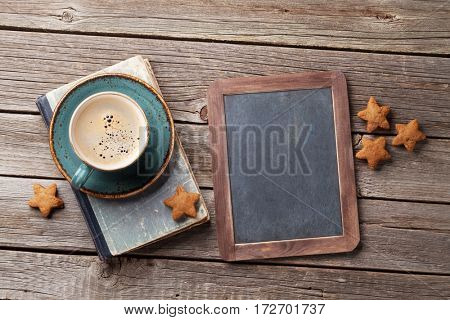 Coffee cup and cookies on wooden table. Top view with chalkboard for your text