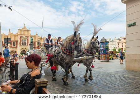 KRAKOW POLAND - JULY 27 2013: Traditional horse carriage with passengers seeing the sights on Krakow's main market square.