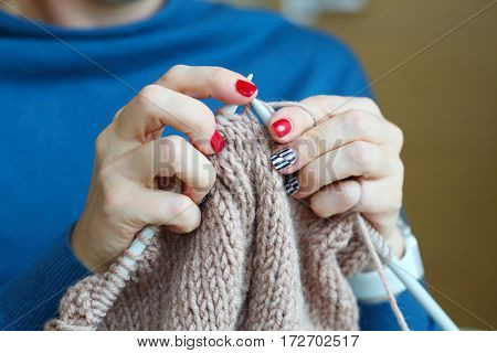 Hands of knitting woman with red manicure, close up view, noface