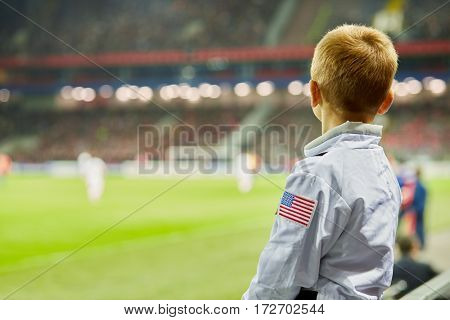 Little boy watch soccer game at stadium, rear view.