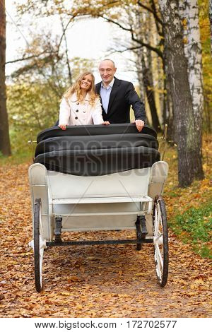 Happy pair are in white coach in autumn yellow park during romantic walk