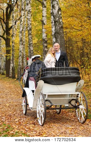 Happy pair are in coach with horse and coachman in autumn park