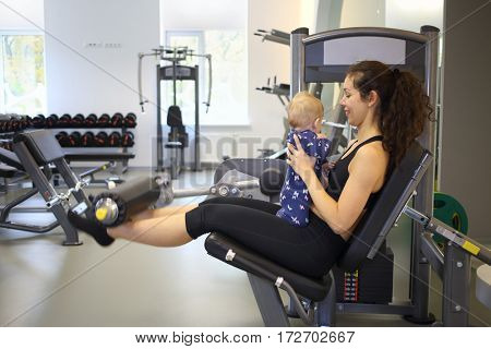 Mother shakes muscles on the simulator with the baby in her arms in the gym