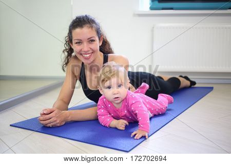 Happy mother and kid lying on a blue mat in the gym