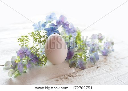 Easter decoration with flowers and a pink egg on a white wooden table