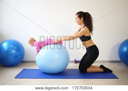 Mother and baby doing exercises on the big blue ball in the gym