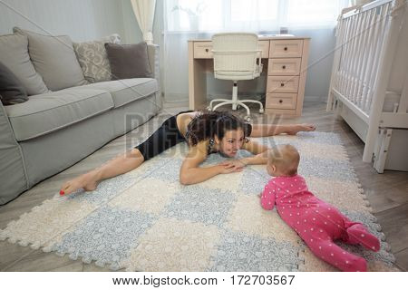 Smiling woman sitting on the splits leaned forward to the baby lying on stomach in the room