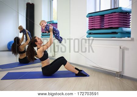 Mother in sportswear sitting picks up little baby near the mirror in the gym