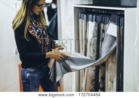 Designer choosing fabric for curtains, color image