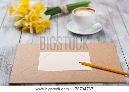 A cup of coffee next to the spring white flowers on wooden texture. Space for text.