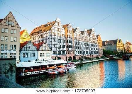 Gdansk Poland - July 18 2014: Old historic granaries on the Granary Island with a restaurant on the water. Embankment of Gdansk is a tourist attraction for visitors.