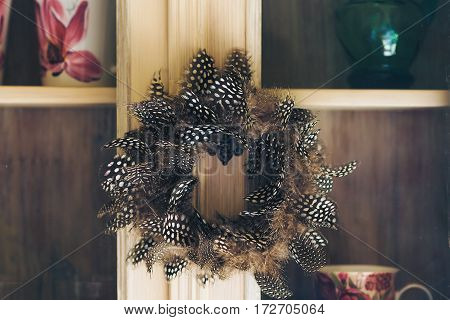 Decorative wreath with feathers on the kitchen furniture.