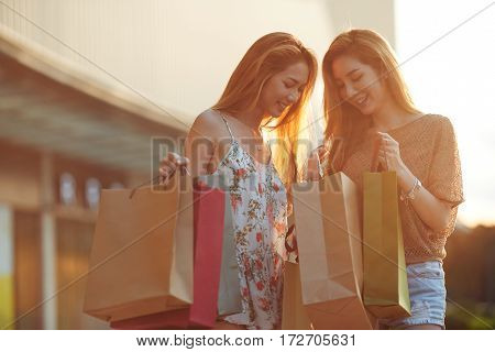 Happy Vietnamese female friends with many shopping bags