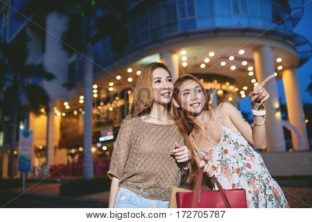 Lovely Asian girls walking in the streets of night city