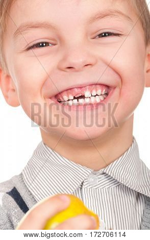 Emotional portrait of happy little boy with fresh yellow apple. Funny child eating fruit while laughing, isolated on white background.