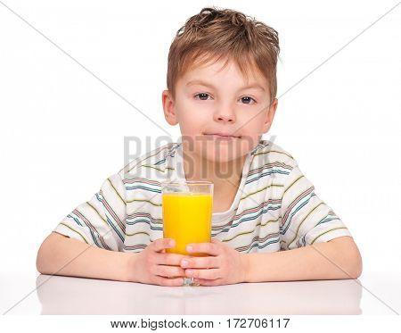 Portrait of happy little boy drinking refreshing orange juice. Smiling child with glass of fresh lemonade.