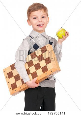 Emotional portrait of caucasian little boy with chessboard and apple. Funny child holding a game of chess in his arms while laughing. Cute smart kid, isolated on white background.
