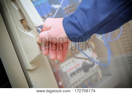 The hand of man in overalls, opens the door to technical cupboard.